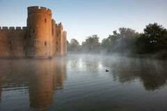 Stunning moat and castle in Autumn Fall sunrise with mist over m Royalty Free Stock Photos