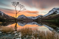 Stunning Morning Sunrise At Buttermere In The Lake District, UK. Vibrant orange sunrise with moving clouds and snowcapped mountains reflecting in calm still royalty free stock image