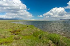 A stunning lake. A stunning mountain lake Son-Kul, with amazing clouds and blue skies Royalty Free Stock Images