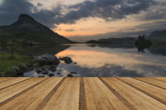 Stunning mountain and lake sunrise reflections beautiful landsca. Beautiful sunrise reflected in calm Lakes landscape with wooden planks floor Royalty Free Stock Images