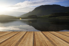 Stunning mountain and lake sunrise reflections beautiful landsca. Beautiful sunrise reflected in calm Lakes landscape with wooden planks floor Royalty Free Stock Photo