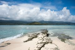 Natural Mystery Island. Stunning mountain landscape, pristine Pacific Ocean waters, and shoreline rock at remote beach on Mystery Island, Vanuatu Stock Image