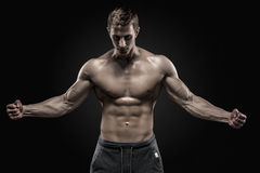 Stunning muscular man showing perfect abs, shoulders, biceps, triceps, chest Stock Images