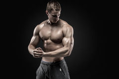 Stunning muscular man showing perfect shoulders, biceps, triceps, chest. Stunning muscular man showing six pack abs, perfect abs, shoulders, biceps, triceps and Royalty Free Stock Photo