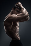 Stunning muscular young men bodybuilder looking behind Royalty Free Stock Photos