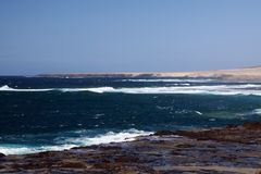 Stunning natural viewpoint with bare dry hills, turquoise lagoon and furious wild sea at north-west coast of Fuerteventura, Canary royalty free stock image