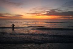 Stunning Ocean Sunset. A stunning sunset over the ocean with person gazing royalty free stock photo