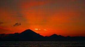 Stunning orange sunset over Mount Agung, Bali. Stunning orange sunset over Mount Batur,  Bali, Indonesia. Summer holiday photo Royalty Free Stock Photography