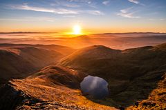 A stunning orange yellow sunrise from Sharp Edge on Blencathra, Lake District, Cumbria with reflection in lake tarn and cloud. Stunning orange yellow sunrise stock images