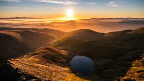 A stunning orange yellow sunrise from Sharp Edge on Blencathra, Lake District, Cumbria with reflection in lake tarn and cloud. Stunning orange yellow sunrise royalty free stock photography