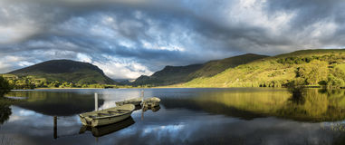 Stunning panorama lake landscape with rowing boats in foreground Royalty Free Stock Images