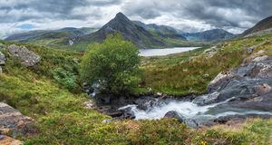 Stunning panorama landscape image of stream flowing over rocks near Llyn Ogwen in Snowdonia during eary Autumn with Tryfan in. Beautiful panorama landscape image royalty free stock image