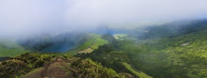 Stunning panoramic view on volcanic lakes. Green Lagoa de Santiago and blue Lagoa Azul with Sete Cidades village. Partially covered by fog mist and clouds. Sao royalty free stock image