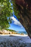 Stunning paradise beach at anse lazio, praslin, seychelles 3. Walking through a hole to a dream beach with white sand, golden granite rocks, palm trees Royalty Free Stock Photography