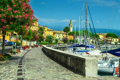Spectacular promenade with colorful oleander flowers, Toscolano-Maderno, Italy. Stunning paved walkway with colorful Mediterranean flowers. Luxury yachts and Royalty Free Stock Photos