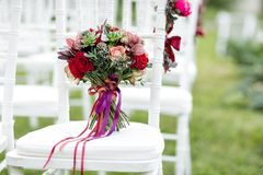 Stunning red bridal bouquet on white chair. Wedding ceremony. Mix of succulents, orchids and roses Stock Photo