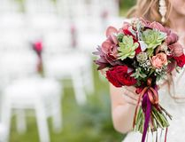 Stunning red bridal bouquet on white chair. Wedding ceremony. Mix of succulents, orchids and roses. copy space Stock Photography
