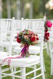 Stunning red bridal bouquet on white chair. Wedding ceremony. Mix of succulents, orchids and roses Royalty Free Stock Images