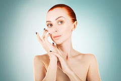 Stunning red haired woman skin health concept, blue background Royalty Free Stock Photography