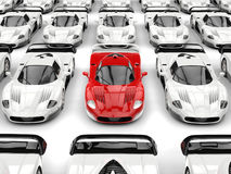Stunning red modern concept sports car stands out in a sea of white sports cars. Isolated on white background Stock Photos