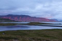 Stunning red mountain behind Grundarfjordur town. Stunning red mountain behind Grundarfjordur town lit up by the sunset. Artistic photo stock image