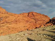 Stunning red orange desert mountains against cloudy gray sky stock images