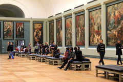 Stunning room of masterpieces with visitors gazing at them,The Louvre,Paris,2016. Gorgeous exhibits of priceless masterpieces lining walls of long,narrow room Stock Photo
