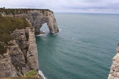 A beautiful cliff arch in etretat, normandy, france. A stunning seascape in etretat, normandy, france, with a limestone cliff arch closeup reaching out in the Royalty Free Stock Image