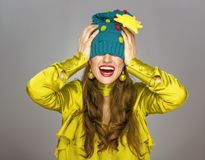 Woman on grey Christmas hat stretched over eyes. Stunning season. smiling elegant woman on grey with funny Christmas hat stretched over eyes stock photography