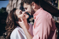 Stunning sensual outdoor portrait of young stylish fashion couple in love. Woman and men embrace and want to kiss each other. They are smiling and looking to Royalty Free Stock Image