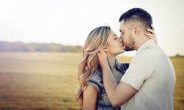 Stunning sensual young couple in love kissing at the sunset in s. Stunning sensual young couple in love posing in summer field, happy lifestyle concept stock photo