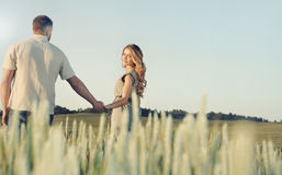 Stunning sensual young couple in love posing in summer field holding hands. Stunning sensual young couple in love posing in summer field, happy lifestyle concept royalty free stock photography