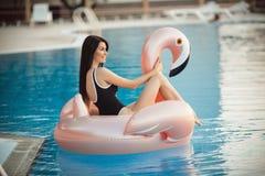 Stunning woman is wearing black bikini sitting in swimming pool with blue water on a pink flamingo mattress, summer royalty free stock photo