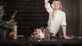 Stunning slow motion footage of an attractive delicate young woman. She is sitting on the table with gorgeous bouquet. Next to her. Throwing a handful of petals stock video footage