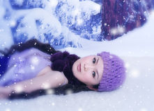Stunning in the Snow. A gorgeous, young Asian woman lays back in the snow in a high fashion pose Stock Photo