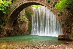 Stunning spring landscape.Paleokarya, old, stone, arched bridge, between two waterfalls. stock photos