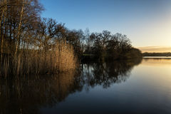 Stunning Spring sunrise landscape over lake with reflections and Stock Images