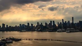 Stunning steady time lapse panorama of gray rain clouds moving in morning orange sunrise sky over New York ocean skyline. Stunning steady time lapse panorama of stock footage