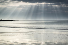 Stunning sun rays bursting from sky over empty yellow sand beach Stock Photography