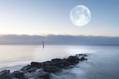 Stunning sunrise landscape over rocks in sea with super moon Royalty Free Stock Photo