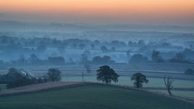Stunning sunrise over fog layers in countryside landscape Stock Photography