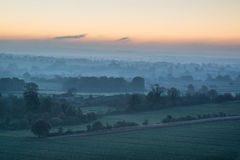 Stunning sunrise over fog layers in countryside landscape Stock Photo