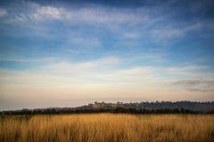 Stunning sunrise over medieval castle in distant landscape Stock Images
