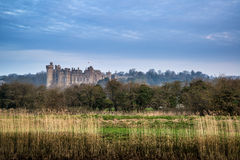 Stunning sunrise over medieval castle in distant landscape Royalty Free Stock Image
