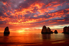 Stunning sunrise over the ocean. With beautiful red clouds and a few cliffs standing out of the water Royalty Free Stock Photos