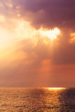 Stunning Sunrise Over The Sea. With fantastic sunbeam through the black stormy cloud royalty free stock images