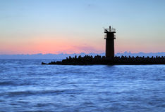 Stunning sunrise over sea with lighthouse. Royalty Free Stock Photos