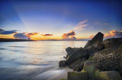 Stunning sunrise on the tropical sandy beach. mossy pipe line and lighthouse background with sunlight ray of light.  Stock Photos