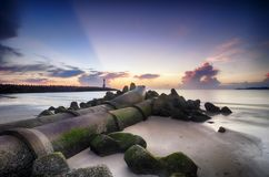 Stunning sunrise on the tropical sandy beach. mossy pipe line an. D lighthouse background with sunlight ray of light royalty free stock photography