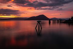 A stunning sunset across the flat calm waters just off the coast of Wrangell, Alaska, the sky appears to be on fire and the. Beautiful pinks, reds  and orange royalty free stock photo